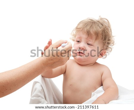 baby is crying and does not want to eat from a spoon, which gives mom - stock photo