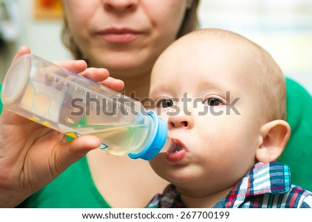 baby is drinking the beverage from the bottle