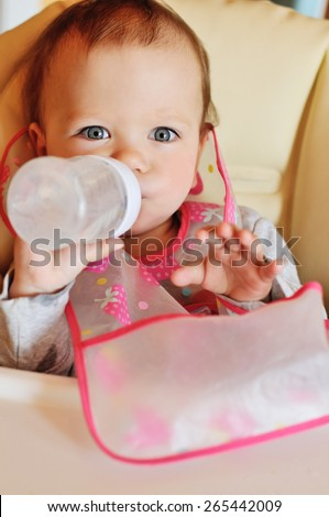 baby is drinking water from the bottle - stock photo