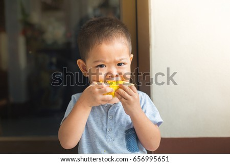 baby is eating corn by himself. it is the favorite food.