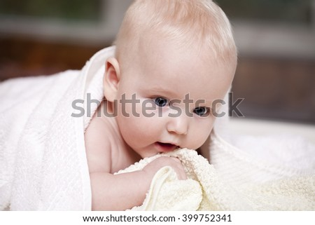 baby is hiding under the white blanket  - stock photo