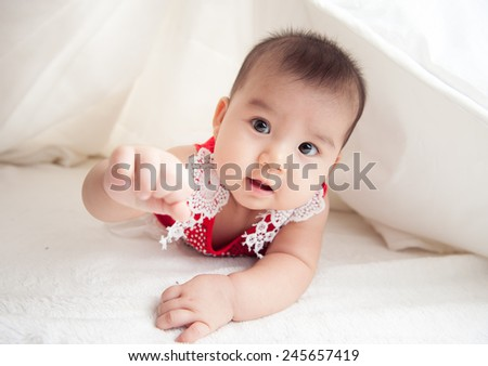 baby is hiding under the white blanket. bright portrait of adorable baby. asian baby in the room - stock photo