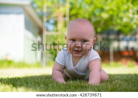 baby is lying on the grass in the garden and smile