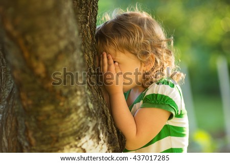 baby is playing hide-and-seek hiding face - stock photo