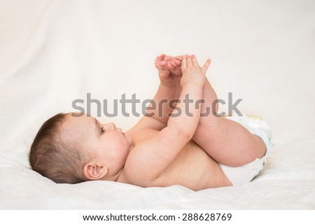 baby is playing with her feet Isolated white background