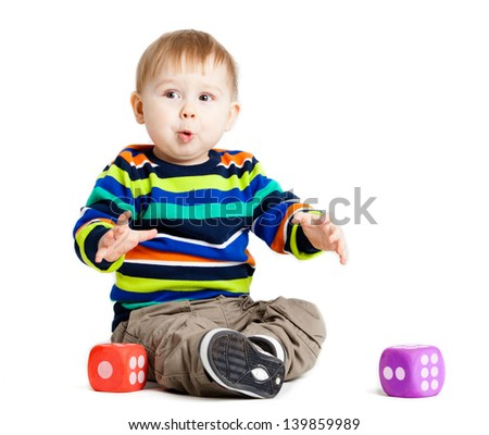 baby is playing with  toys over white background. Funny little kid playing with cup toys - stock photo