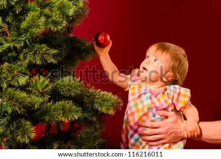 baby is reaching for christmas toy near tree