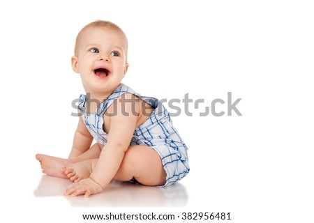 Baby is sitting on floor, isolated on white - stock photo