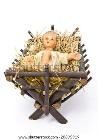Baby Jesus figurine lying in manger on hay on white background - stock photo