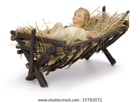 Baby Jesus figurine lying in manger on hay on white background. Clipping path incl. - stock photo
