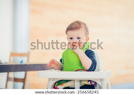 baby kid child boy is eating using his hand - stock photo