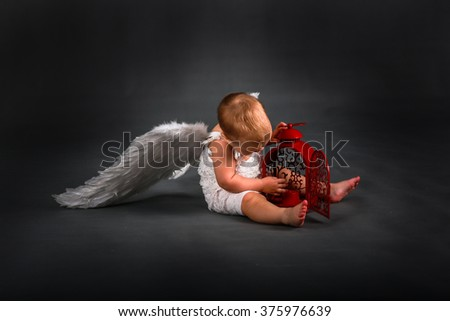 baby Kid in white dress with angel wings with red light , the concept of Valentine's Day, look candle - stock photo