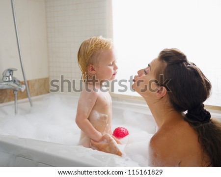 Baby kissing mother while washing in foam filled bathtub - stock photo