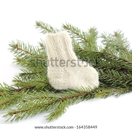 baby knitted woolen sock near spruce branches - stock photo
