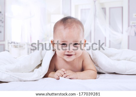 Baby laughing under blanket inside the house. shot in the bedroom - stock photo