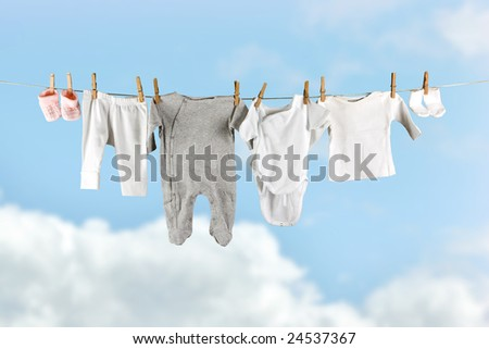 Baby laundry hanging in the sky on a clothesline - stock photo