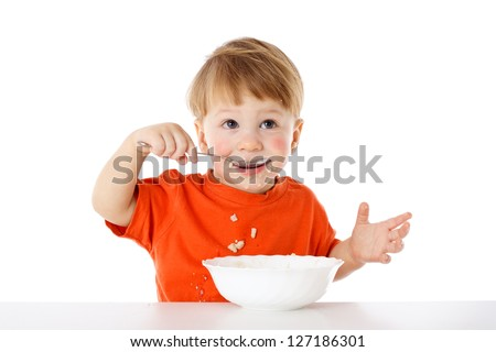 Baby learning to feed herself - eating the oatmeal with a spoon, isolated on white