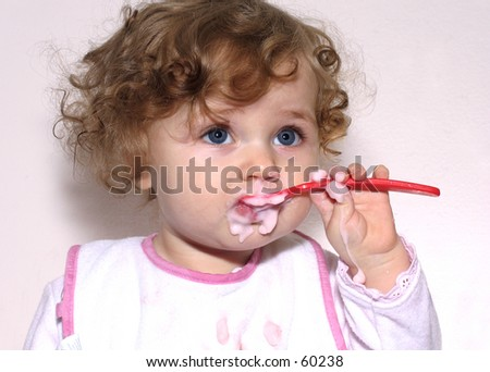 baby learning to feed herself with a spoon on white background - stock photo