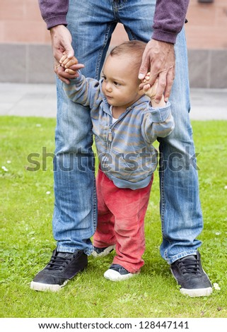 Baby learning to walk and making his first steps holding the hands of his father. - stock photo
