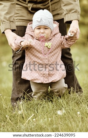 Baby learns to walk in the grass. Vintage style. - stock photo