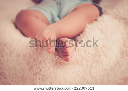 Baby legs and bottom in diaper and blue body suit - stock photo