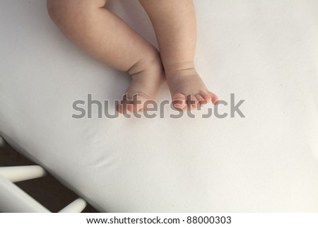 baby legs in a crib - stock photo