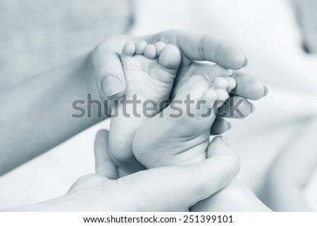 baby legs in mother hands - stock photo
