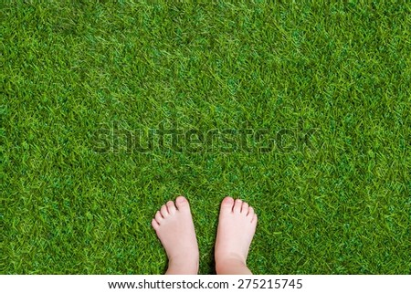 Baby legs standing  on green grass having fun outdoors