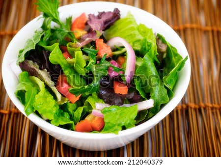 Baby lettuces mixed with crisp red bell pepper and Spanish onion.  - stock photo