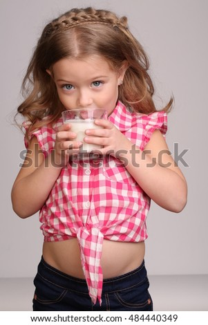 Baby licking milk. Close up. Gray background