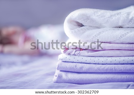 baby linen on the bed - stock photo