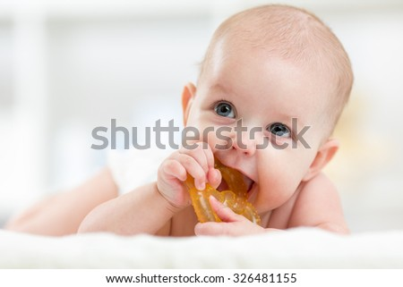 baby little child lying on bed weared diaper with teether - stock photo