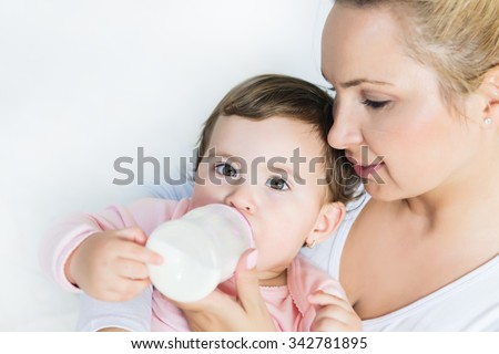 Baby little girl drinking a milk from bottle in the mom's arms.Shallow doff - stock photo