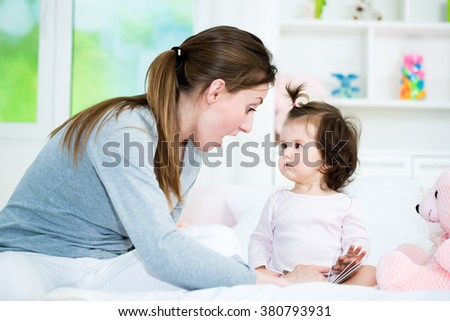 Baby little girl looking at mom while she reading the interesting story from the book.Shallow doff