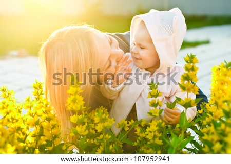 baby looking at her mother and smiling in the garden in sunlight - stock photo