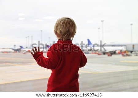 baby looking at planes in the airport - stock photo