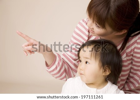 Baby Looking At The Direction In Which The Mother Pointing - stock photo