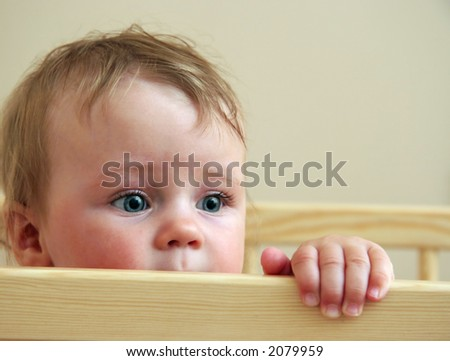 baby looking from his bed - stock photo