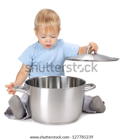 Baby looking inside saucepan. Isolated on white background