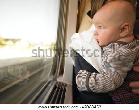 Baby looking out train window while being held by adult. Horizontally framed shot. - stock photo