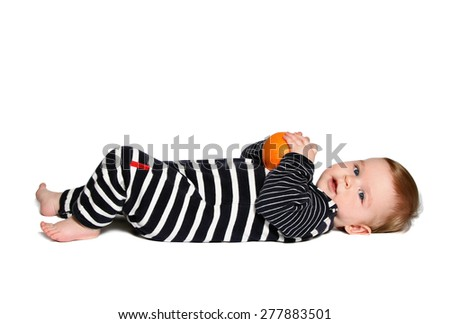 baby lying down and holds orange, looking at camera on white background - stock photo