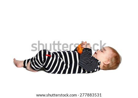 baby lying down holds and looking at orange on white background - stock photo