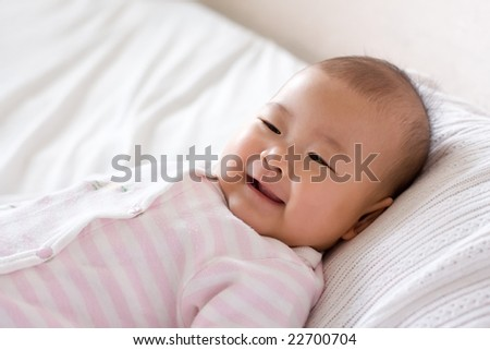 Baby lying in bed, giggling