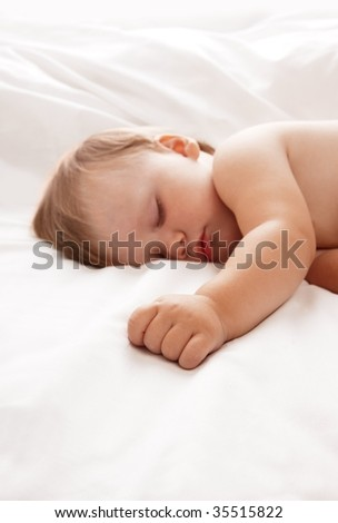 Baby lying in white sheets - stock photo