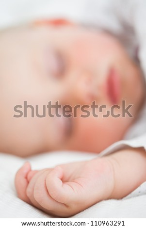 Baby lying on a bed while closing her eyes in a bright room - stock photo