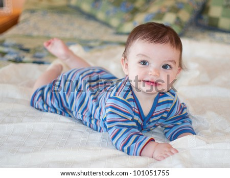 Baby lying on bed posing for picture wearing blue striped outfit