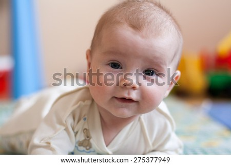 baby lying on floor with kids toys, smiling baby, surprised expression, frustrated expression - stock photo