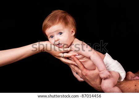 Baby lying on parents hands looking very cute - stock photo