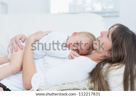 Baby lying on the chest of a mother in living room