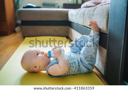 baby lying on the floor with his feet up and drinking watter from a bottle - stock photo